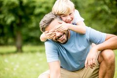 Son covers father`s eyes. While playing and has fun in the park stock images