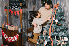 Son and dad decorating the christmas tree at home Stock Images