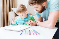 Son and dad drawing together on the table. Son and dad sitting and drawing together on the table Stock Image