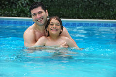 Son and Dad Enjoying Pool. Son and dad enjoying the swimming pool royalty free stock photos
