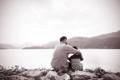 Son and dad fishing at dam. Black and white tone royalty free stock images