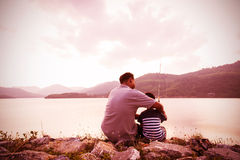 Son and dad fishing at dam. Vintage tone stock photography