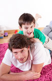 Son and dad having fun. On the floor Stock Image