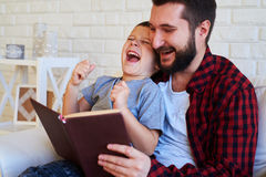 Son and dad laughing and reading a book. A mid shot of son a dad laughing and reading a book in brown cover. Father wearing red checkered shirt and son wearing Stock Images