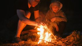 Son and dad light a fire in the forest. Family camping. Son and dad light a fire in the forest stock photo