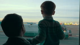 Son and dad looking at airport area through the stock video footage
