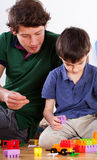 Son and dad playing. A dad playing with his son with colourful blocks and toys Stock Image