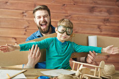 Son and dad playing together. Funny portrait of bearded father and cute little son in aviator goggles and with carton airplane wings behind his back playing Royalty Free Stock Photo