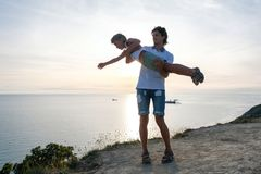 Son on the dad`s hands on a mountain with seaside. Playing together at sunset. Fun pastime. Son on the dad`s hands on a mountain with seae. Playing together at Royalty Free Stock Photo