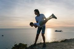 Son on the dad`s hands on a mountain with seaside. Playing together at sunset. Fun pastime. Son on the dad`s hands on a mountain with seaside. Playing together Royalty Free Stock Photo