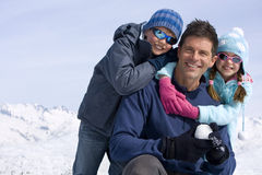 Son and daughter (6-8) embracing father in snow field, smiling, portrait, mountain range in background Stock Image