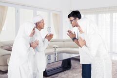 Son and daughter greetings their parents during Eid al-fitr celebration in living room