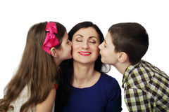 Son and daughter kiss mother. Boy and girl kiss smiling women from two sides isolated on white background - Son and daughter love their mother Stock Images