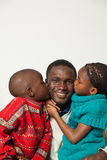 Son and daughter kissing her father. Black son and daughter kissing Stock Image