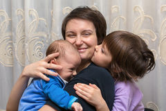 Son and daughter kissing her mother.  royalty free stock photo