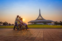 Son and daughter take her mother. BANGKOK,THAIL AND-FEBRUARY 19: Son and daughter take her mother on wheel chair for exercise and walking for relax with warm Royalty Free Stock Photo