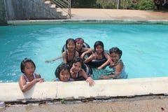 Son de goce y felices en la piscina foto de archivo libre de regalías