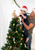 Son decorating the christmas tree with his father. Cute son decorating the christmas tree with his father in the living room royalty free stock images