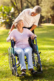 Son disabled mother. Loving middle aged son taking his disabled mother for a walk at the park Stock Images