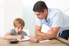 Son doing homework while father standing by Stock Photo