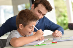 Son doing homewrok with his father beside. Man helping son with homework royalty free stock image