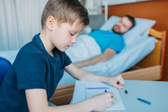 Son drawing pictures while sick father laying on hospital bed at ward. Dad and son Royalty Free Stock Image