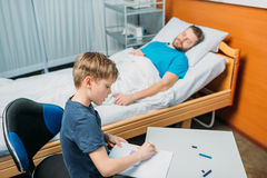 Son drawing pictures while sick father laying on hospital bed at ward. Dad and son Royalty Free Stock Photography