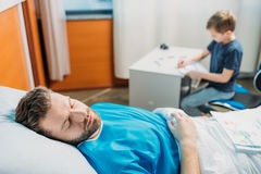 Son drawing pictures while sick father laying on hospital bed at ward. Dad and son Stock Image
