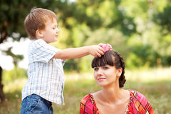 Son dressing a knitted crown on  his mother. Stock Photos