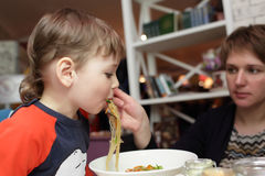 Son eating noodles. From her mother's hands Stock Photo