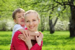 Son embraces behind mother for neck. In park in spring Royalty Free Stock Photography