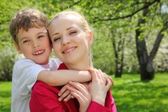 Son embraces behind mother for neck. In park in spring Royalty Free Stock Image
