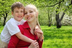 Son embraces behind mother in park. In spring Royalty Free Stock Photos