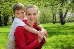 Son embraces behind mother in park. Son embraces behind mother  in park in spring Royalty Free Stock Photos