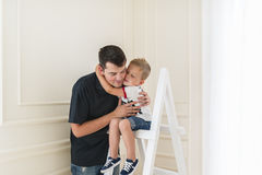 The son embraces the beloved daddy. Little boy is sitting on a step-ladder. Father and son are smiling while spending time together. Little boy is sitting on a stock photo