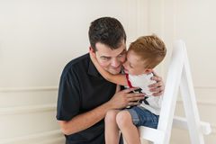 The son embraces the beloved daddy. Little boy is sitting on a step-ladder. Father and son are smiling while spending time together. Little boy is sitting on a royalty free stock images