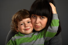 The son embraces favorite mum. Gray background stock photography
