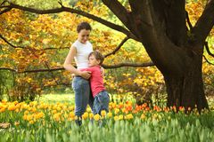 Son embraces mother in garden among tulips. Son embraces mother in garden in spring among blossoming tulips royalty free stock photo