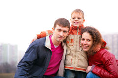Son embraces parents outdoor in city Royalty Free Stock Photo