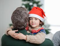 Son Embracing Father During Christmas. Portrait of son embracing father during Christmas at home Royalty Free Stock Image