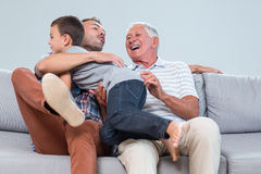 Son embracing father in living room Stock Images