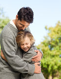Son embracing his father. In a park stock image