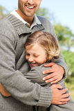 Son embracing his father. In the park stock photography