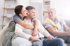 Son embracing his father. Grandfather sitting on sofa and smiling Royalty Free Stock Images