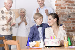 Son embracing his mother. During her birthday party royalty free stock photos