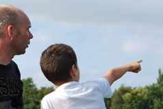 Son explaining to father. A child points to something in the distance, explaining to his father Royalty Free Stock Images