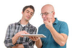 A son explains to his father the digital tablet. On the white background royalty free stock images