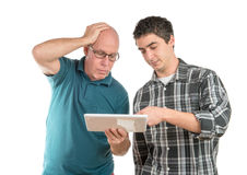 A son explains to his father the digital tablet. On the white background Stock Image