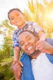 Son för blandat lopp och afrikansk amerikanfader Play Piggyback Outdoorsdoors arkivbild