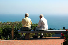 Son and Father. A son sits with his aging father on a bench overlooking the Pacific Ocean Stock Photography